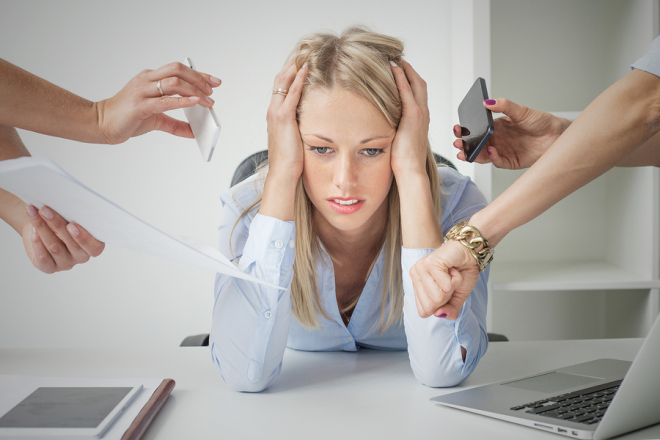 Depressed woman overloaded with stuff at work